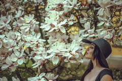Menina bonita com cabelo preto em um vestido preto em um fundo de uma flor da magnólia Fotografia de Stock Royalty Free