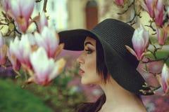 Menina bonita com cabelo preto em um vestido preto em um fundo de uma flor da magnólia Fotografia de Stock