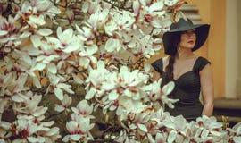 Menina bonita com cabelo preto em um vestido preto em um fundo de uma flor da magnólia Imagem de Stock