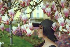 Menina bonita com cabelo preto em um vestido preto em um fundo de uma flor da magnólia Foto de Stock Royalty Free