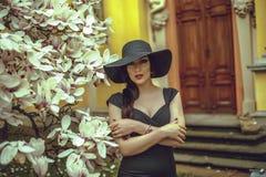 Menina bonita com cabelo preto em um vestido preto em um fundo de uma flor da magnólia Fotos de Stock