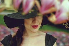 Menina bonita com cabelo preto em um vestido preto em um fundo de uma flor da magnólia Imagens de Stock