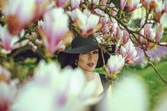 Menina bonita com cabelo preto em um vestido preto em um fundo de uma flor da magnólia Imagem de Stock Royalty Free