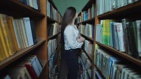 A menina bonita com cabelo preto longo vai beetween as prateleiras na biblioteca video estoque