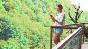 Menina bonita com cabelo trançado louro na ponte do ar sobre o precipício coberto com as florestas brilhantes grossas da folha, g filme