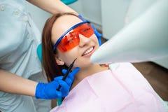 A menina bonita com cabelo vermelho está sentando-se na cadeira dental Tratamento e prevenção de doenças dentais foto de stock