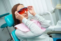A menina bonita com cabelo vermelho está sentando-se na cadeira dental Tratamento e prevenção de doenças dentais fotografia de stock