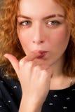 Menina bonita com cabelo vermelho que lambe seu dedo Fotos de Stock Royalty Free