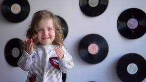 A menina bonita com cachos sorri na frente da câmera Criança que cola para fora a língua, retrato sobre o cinza vídeos de arquivo