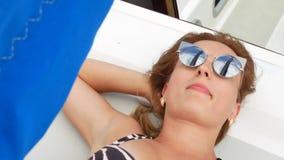 Menina bonita bonita com claro - mentiras marrons do cabelo no iate e no banho de sol video estoque