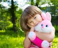 Menina bonita com coelho macio cor-de-rosa Foto de Stock
