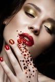 Menina bonita com composição da noite, bordos vermelhos nos cristais de rocha e pregos do tratamento de mãos do projeto Face da b Fotografia de Stock