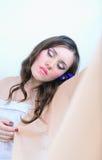 Menina bonita com composição em um pano branco com telas Imagem de Stock