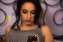 Menina bonita com a composição profissional que fuma um sigarette e que olha seu telefone Foto de Stock Royalty Free