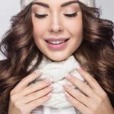 Menina bonita com composição, tratamento de mãos do projeto e sorriso delicados no chapéu branco da malha Imagem morna do inverno Fotografia de Stock Royalty Free
