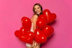 A menina bonita com coração deu forma aos balões de ar, comemorando o dia do ` s do Valentim foto de stock