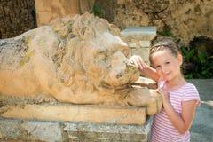 Menina bonita com escultura do leão Fotos de Stock Royalty Free