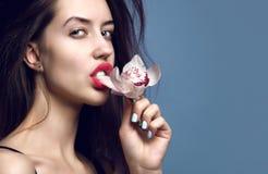 Menina bonita com flores da orquídea Cara da mulher do modelo da beleza no fundo roxo fotos de stock royalty free