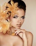 Menina bonita com flores douradas. Beleza Woman Face modelo. Por fotografia de stock royalty free