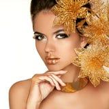 Menina bonita com flores douradas. Beleza Woman Face modelo. Por Foto de Stock Royalty Free