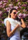 Menina bonita com flores, mágica da mola Flores do rosa de Sakura Com pele branca do encanto, e óculos de sol Fotografia de Stock Royalty Free