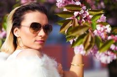 Menina bonita com flores, mágica da mola Flores do rosa de Sakura Com pele branca do encanto, e óculos de sol Fotos de Stock Royalty Free