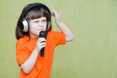 Menina bonita com fones de ouvido em sua cabeça e em um microfone em h Foto de Stock