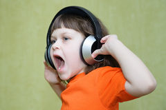 Menina bonita com fones de ouvido no seu principal e em uma camisa alaranjada s Fotografia de Stock Royalty Free
