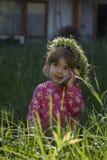 Menina bonita com a grinalda da cabeça de flores e fala em seu telefone celular no parque Foto de Stock