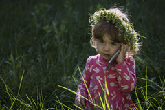 Menina bonita com a grinalda da cabeça de flores e fala em seu telefone celular no parque Imagem de Stock
