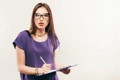 Menina bonita com lápis e papel que pensa sobre algo fotos de stock