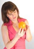 Menina bonita com a laranja nas mãos Imagem de Stock