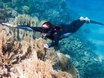 A menina bonita com monofin nada acima dos corais Imagens de Stock Royalty Free