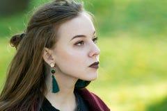 Menina bonita com o batom escuro que olha ao lado Iluminação natural do contorno fotografia de stock