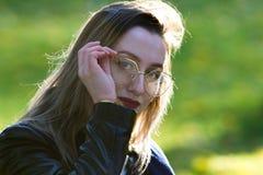 Menina bonita com o batom vermelho que olha na câmera e que fixa seus vidros Iluminação natural do contorno imagem de stock