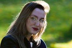 Menina bonita com o batom vermelho que olha na câmera Iluminação natural do contorno imagens de stock