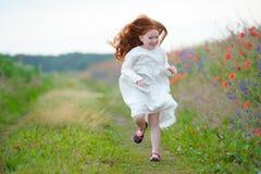 Menina bonita com o cabelo dourado longo que corre para o smilin engraçado Foto de Stock Royalty Free