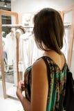 Menina bonita com o cabelo escuro que está na frente de uma loja luxuosa e que olha uma coleção nova Imagens de Stock