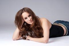 Menina bonita com o cabelo longo que encontra-se no assoalho imagens de stock royalty free