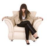 Menina bonita com o cabelo longo que senta-se na poltrona. Fotografia de Stock Royalty Free