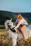 Menina bonita com o cavalo branco no campo Foto de Stock
