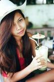 Menina bonita com o chapéu, bebendo o suco de abacaxi fresco e refrescando, férias das férias de verão Imagens de Stock