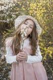 Menina bonita com o chapéu em flores dos cheiros da natureza imagem de stock royalty free