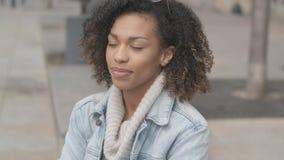Menina bonita com o corte de cabelo afro que senta-se no banco na rua da cidade filme