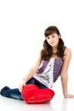 Menina bonita com o descanso vermelho dado forma coração Fotografia de Stock Royalty Free