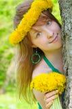 Menina bonita com o diadem dos dentes-de-leão amarelos Fotografia de Stock