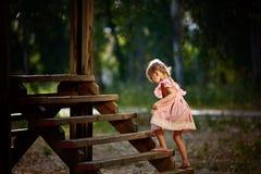 Menina bonita com o jogo engraçado das expressões da cara, escalando acima no escadas de madeira imagens de stock royalty free