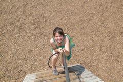 Menina bonita com o jogo engraçado das expressões da cara, escalando acima no escadas de madeira imagens de stock