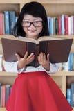 Menina bonita com o livro na biblioteca Imagens de Stock