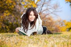 Menina bonita com o livro que encontra-se na grama Fotografia de Stock Royalty Free